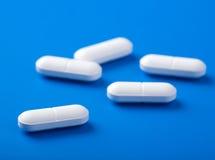 Weiße Pillen über Blau Stockfoto