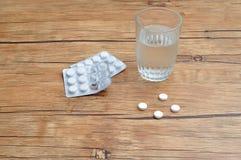 Weiße Pillen angezeigt mit einem Glas Wasser und zwei Blisterpackungen Stockfotos
