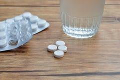 Weiße Pillen angezeigt mit einem Glas Wasser und zwei Blisterpackungen Stockbilder