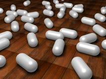Weiße Pillen auf dem Fußboden Stockfotografie