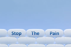 Weiße Pillen auf einem blauen Hintergrund mit dem Wörter ` stoppen das Schmerz ` Lizenzfreie Stockbilder