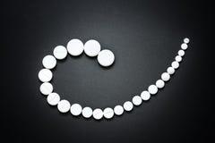 Weiße Pillen auf grauem Hintergrund Stockfotografie
