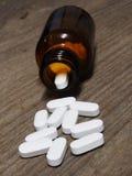 Weiße Pillen, die aus einem Tablettenfläschchen auf Holztisch heraus verschüttet werden Lizenzfreie Stockfotos