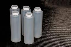 Weiße Plastikbehälter mit Deckeln auf Kohlenstofffaser lizenzfreie stockfotografie