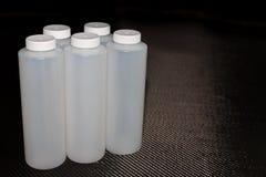 Weiße Plastikbehälter mit Deckeln auf Kohlenstofffaser stockbilder