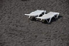 Weiße Plastikbetten des Aufenthaltsraums auf schwarzem Sandstrand Stockfotografie