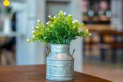 Weiße Plastikblumen in einem Topf auf einer Tabelle lizenzfreie stockfotos