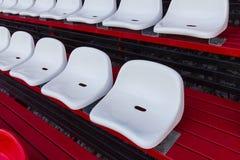 Weiße Plastiksitze im Stadion Stockfoto