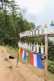 Weiße Plastikstraßenrandgebetsräder auf dem Weg zu Kloster Taktshang Palphug (das Nest des Tigers), Bhutan lizenzfreie stockfotografie