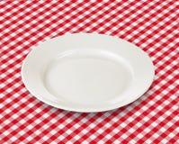 Weiße Platte über roter Picknicktischdecke Stockbild