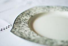 Weiße Platte auf der Tischdecke Stockfotografie