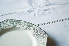 Weiße Platte auf der Tischdecke Stockbild