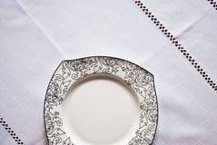 Weiße Platte auf der Tischdecke Stockfoto