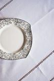 Weiße Platte auf der Tischdecke Lizenzfreies Stockfoto