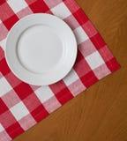 Weiße Platte auf hölzerner Tabelle mit roter Tischdecke Stockfotos