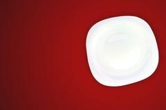 Weiße Platte auf rotem Hintergrund. Stockbilder