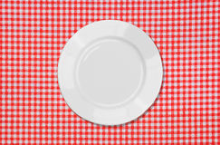 Weiße Platte auf roter und weißer Tischdecke Lizenzfreie Stockfotografie