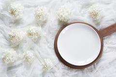 Weiße Platte der Eleganz mit Blumendekor auf weißem hölzernem Brett rustikaler Zauntritt Beschneidungspfad eingeschlossen Lizenzfreies Stockfoto