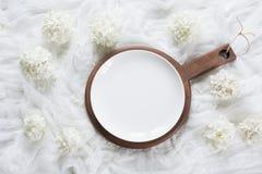 Weiße Platte der Eleganz mit Blumendekor auf weißem hölzernem Brett rustikaler Zauntritt Beschneidungspfad eingeschlossen Lizenzfreie Stockfotografie