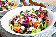 Weiße Platte des köstlichen Gemüsesalats auf hölzernem Stockfotografie
