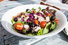 Weiße Platte des köstlichen Gemüsesalats auf hölzernem Stockbild