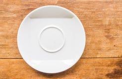 Weiße Platte genommen vertikal gesetzt auf ein hölzernes Braun Lizenzfreies Stockbild