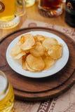 Weiße Platte mit Chips auf einem runden hölzernen Brett Stockbild
