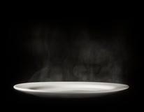 Weiße Platte mit Dampf auf schwarzem Hintergrund Lizenzfreie Stockfotos