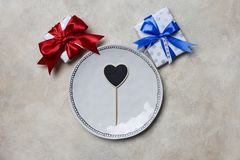 Weiße Platte mit Geschenkboxen mit den roten und blauen Bändern am weißen Hintergrund lizenzfreies stockfoto