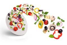 Weiße Platte mit Salat im Flug Lizenzfreies Stockfoto
