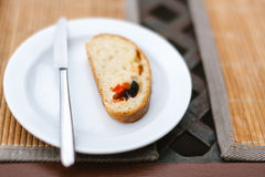 Weiße Platte mit Scheibe brot mit Scheiben des Pfeffers und der schwarzen Olive Stockbild