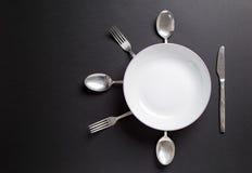 Weiße Platte mit Tischbesteck über schwarzem Hintergrund Nützlich als backgr Lizenzfreies Stockfoto