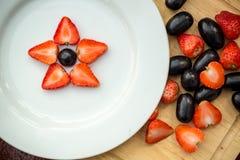 Weiße Platte mit Trauben und Erdbeeren, Sternform Stockfotos