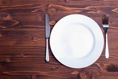 Weiße Platte und Gabel nahe bei einem Messer auf einer Draufsicht des hölzernen Brettes Lizenzfreie Stockbilder