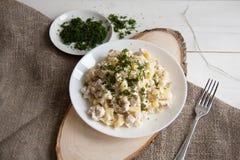 Weiße Platte voll des Salats gemacht mit Kartoffel, Huhn und Essiggurken Stockfoto