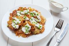 Weiße Platte von Kartoffelpfannkuchen oder von Latke Stockfotos