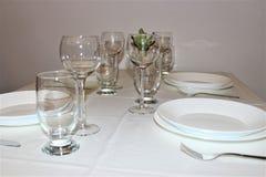 Weiße Platten, Gläser, Tischbesteck auf einer weißen Tischdecke stockfotografie