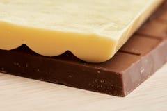 Weiße poröse Schokolade liegt auf der schwarzen Schokoladennahaufnahme Stockbilder