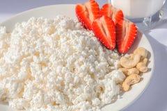 Weiße Porzellanplatte mit Käse und reife Erdbeeren, Acajoubäume und transparente Glasschale mit Milch stockfotos