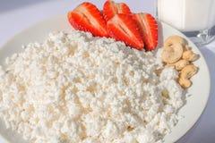 Weiße Porzellanplatte mit Käse und reife Erdbeeren, Acajoubäume und transparente Glasschale mit Milch stockfoto