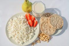 Weiße Porzellanplatte mit Käse und reife Erdbeeren, Acajoubäume und transparente Glasschale mit Milch grüne Birnen und Cracker lizenzfreies stockfoto