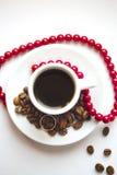 Weiße Porzellanschale mit Kaffee und Kaffeebohnen mit Silberhochzeitringen und -ROT Lizenzfreie Stockbilder