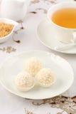 Weiße Pralinen mit Tee Stockfotografie