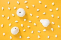 Weiße Pralinen und gemalte Früchte auf gelbem Hintergrund Lizenzfreie Stockfotos