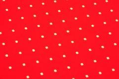 Weiße Punkte auf rotem Stoff Stockfotografie