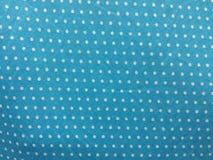 Weiße Punkte des Gewebemusters auf einem cyan-blauen Hintergrund Stockbilder