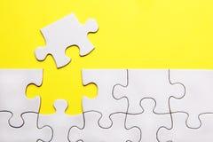 Weiße Puzzlespielstücke auf gelbem Hintergrund Lizenzfreie Stockfotos