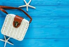Weiße Rattantasche auf blauem Hintergrund modische Bambustasche, Starfish, Oberteile Sommermodeebene legen, Ferien, Reise c lizenzfreie stockfotos