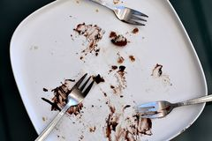 Weiße rechteckige Mattplatte leer und mit den Überresten eines Schokoladenkuchens und -krumen befleckt stockfoto