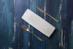 Weiße rechteckige Platte mit Gabel und Messer auf blauem hölzernem backg Stockfotos